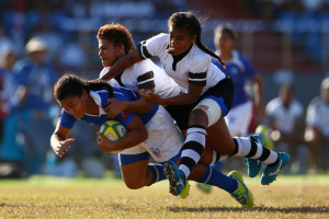 Teuila Aukusitino of Samoa is tackled by Airini Vuidravuwalu and Jiowana Sauto of Fiji during the girls match between Samoa and Fji in the rugby sevens competition at the Apia Park Sports Complex